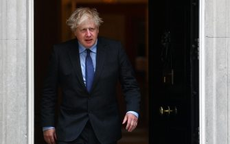epa09271522 British Prime Minister Boris Johnson walks out the door at 10 Downing Street in London, Britain, 14 June 2021. British Prime Minister Johnson announced a month delay to lockdown easing regulations. The UK government is to delay for a further four weeks to full reopening due to a significant rise in Delta variant Covid-19 cases across England.  EPA/ANDY RAIN