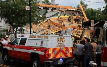 WASHINGTON, DC - JULY 01: Firefighters work to free a man trapped inside a collapsed construction site on July 01, 2021 in Washington, DC. Five people were injured when the multi-story construction site collapsed during a thunderstorm. (Photo by Chip Somodevilla/Getty Images)