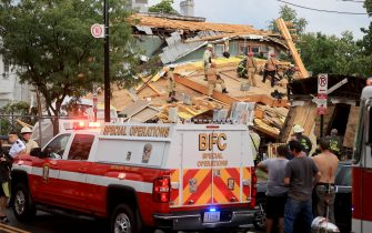 WASHINGTON, DC - JULY 01: Firefighters work to free a man trapped inside a collapsed construction site on July 01, 2021 in Washington, DC. Five people were injured when the two-story construction site collapsed during a thunderstorm. (Photo by Chip Somodevilla/Getty Images)