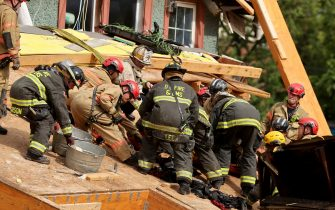 WASHINGTON, DC - JULY 01: Firefighters pull a man out of a pile of debris after he was trapped inside a collapsed construction site on July 01, 2021 in Washington, DC. Five people were injured when the two-story construction site collapsed during a thunderstorm. (Photo by Chip Somodevilla/Getty Images)
