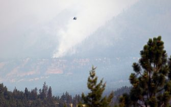 A helicopter flies above a wildfire burning near Lytton, British Columbia, Canada, on Friday, July 2, 2021. Canadian Prime Minister Justin Trudeau called an emergency meeting of a crisis committee to address the wildfires that are raging through the western part of the country as a heat wave shatters records. Photographer: James MacDonald/Bloomberg