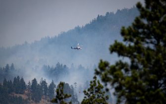A helicopter pilot prepares to drop water on a wildfire burning in Lytton, BC, Canada, on Friday, July 2, 2021. In Lytton, Canada's temperature record was broken on Tuesday when the mercury hit 49.6C (121F). Less than 24 hours later the small village in British Columbia was evacuated, with just minutes notice, as wildfires broke out. Photo by Darryl Dyck/CP/ABACAPRESS.COM