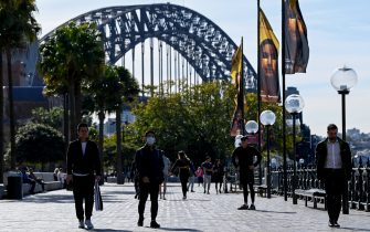 People walk along Circular Quay in Sydney on July 6, 2021, as the city remains in lockdown for a second week to contain an outbreak of the highly contagious Delta Covid-19 variant. (Photo by Bianca De Marchi / AFP) (Photo by BIANCA DE MARCHI/AFP via Getty Images)