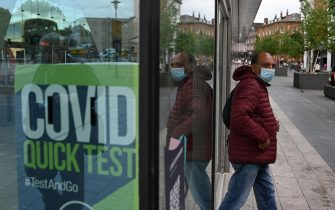 A man wearing a face covering passes a Covid-19 information sign as he exits the Bus Station in Blackburn, north west England on June 16, 2021. - The UK government on Monday announced a four-week delay to the full lifting of coronavirus restrictions in England due to a surge in infections caused by Delta, which first appeared in India. (Photo by Oli SCARFF / AFP)