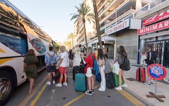Giovani turisti in attesa di salire su un pullman a Maiorca, in Spagna