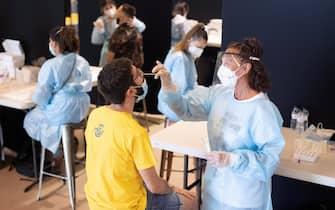 Un'operatrice sanitaria con mascherina e tuta protettiva esegue un tampone in Spagna
