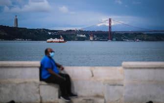 Un uomo, che indossa una mascherina anti-Covid, seduto su una delle sponde del fiume Tago a Lisbona, in Portogallo