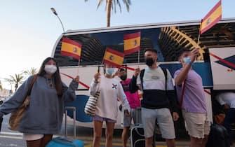 Giovani turisti sventolano le bandiere della Spagna davanti a un pullman, a Maiorca