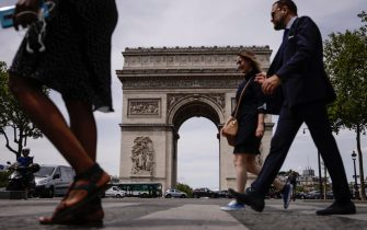 epa09279479 People not wearing protective face masks walk past the Arc of Triomphe in Paris, France, 17 June 2021. France eases some of its coronavirus disease (COVID-19) restrictions starting on 17 June, allowing not to wear a face mask in the streets.  EPA/YOAN VALAT