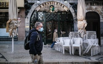 epa08938735 People walk by 'A Brasileira' cafe on the first day of new general confinement takes effect in Lisbon, Portugal, 15 January 2021.  Portugal is facing new stricter lockdown rules to be applied across the country due to the covid-19 pandemic. The country registered 10,556 new cases of infection on 14 January 2021 (a new maximum).  EPA/MARIO CRUZ