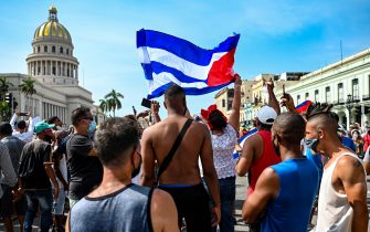 """TOPSHOT - Cubans are seen outside Havana's Capitol during a demonstration against the government of Cuban President Miguel Diaz-Canel in Havana, on July 11, 2021. - Thousands of Cubans took part in rare protests Sunday against the communist government, marching through a town chanting """"Down with the dictatorship"""" and """"We want liberty."""" (Photo by YAMIL LAGE / AFP) (Photo by YAMIL LAGE/AFP via Getty Images)"""