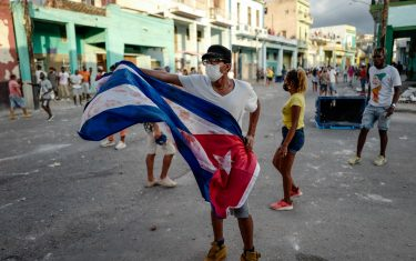"""A man waves a Cuban flag during a demonstration against the government of Cuban President Miguel Diaz-Canel in Havana, on July 11, 2021. - Thousands of Cubans took part in rare protests Sunday against the communist government, marching through a town chanting """"Down with the dictatorship"""" and """"We want liberty."""" (Photo by ADALBERTO ROQUE / AFP) (Photo by ADALBERTO ROQUE/AFP via Getty Images)"""