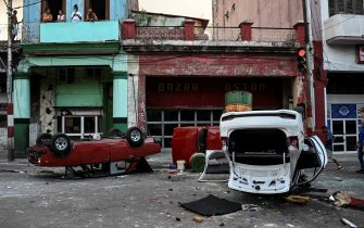 """Police cars are seen overturned in the street in the framework of a demonstration against Cuban President Miguel Diaz-Canel in Havana, on July 11, 2021. - Thousands of Cubans took part in rare protests Sunday against the communist government, marching through a town chanting """"Down with the dictatorship"""" and """"We want liberty."""" (Photo by YAMIL LAGE / AFP) (Photo by YAMIL LAGE/AFP via Getty Images)"""