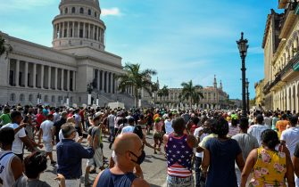 """Cubans are seen outside Havana's Capitol during a demonstration against the government of Cuban President Miguel Diaz-Canel in Havana, on July 11, 2021. - Thousands of Cubans took part in rare protests Sunday against the communist government, marching through a town chanting """"Down with the dictatorship"""" and """"We want liberty."""" (Photo by YAMIL LAGE / AFP) (Photo by YAMIL LAGE/AFP via Getty Images)"""