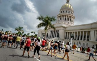 """Cubans march in front of Havana's Capitol during a demonstration against the government of Cuban President Miguel Diaz-Canel in Havana, on July 11, 2021. - Thousands of Cubans took part in rare protests Sunday against the communist government, marching through a town chanting """"Down with the dictatorship"""" and """"We want liberty."""" (Photo by ADALBERTO ROQUE / AFP) (Photo by ADALBERTO ROQUE/AFP via Getty Images)"""