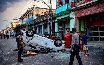 """TOPSHOT - Police cars are seen overturned in the street in the framework of a demonstration against Cuban President Miguel Diaz-Canel in Havana, on July 11, 2021. - Thousands of Cubans took part in rare protests Sunday against the communist government, marching through a town chanting """"Down with the dictatorship"""" and """"We want liberty."""" (Photo by YAMIL LAGE / AFP) (Photo by YAMIL LAGE/AFP via Getty Images)"""