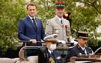French President Emmanuel Macron and French Armies Chief of Staff General Francois Lecointre stand in the command car as they review troops prior to the annual Bastille Day military parade on the Champs-Elysees avenue in Paris on July 14, 2021. (Photo by Ludovic MARIN / POOL / AFP) (Photo by LUDOVIC MARIN/POOL/AFP via Getty Images)