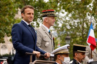 epa09343473 French President Emmanuel Macron (L) and French Armies Chief of Staff General Francois Lecointre (R) stand in the command car as they review troops prior to the annual Bastille Day military parade on the Champs-Elysees avenue in Paris, France, 14 July 2021. France is celebrating its national holiday with thousands of troops marching in a Paris parade and traditional parties around the country, after last year's events were scaled back because of coronavirus fears.  EPA/LUDOVIC MARIN / POOL  MAXPPP OUT
