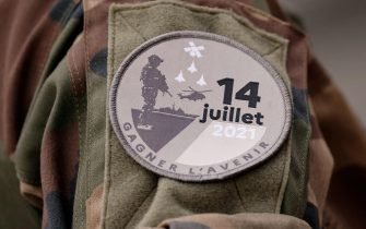 A badge reading 'July 14, 2021' is pictured on the uniform of a French soldier as preparations are made for the annual Bastille Day military parade on the Champs-Elysees avenue in Paris on July 14, 2021. (Photo by Ludovic MARIN / AFP) (Photo by LUDOVIC MARIN/AFP via Getty Images)