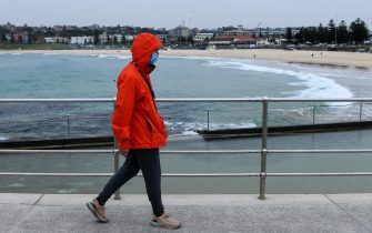 epa09343363 A person wearing a face mask walks along an empty Bondi Beach foreshore in Sydney, Australia, 14 July 2021. Greater Sydney's lockdown has been extended for another two weeks, after another 97 new Covid-19 cases were detected were overnight.  EPA/BIANCA DE MARCHI AUSTRALIA AND NEW ZEALAND OUT