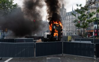 A construction machine is set on fire by demonstrators in order to slow down the progress of riot police at the Gare de l'Es, while on July 14, 2021, 2 days after the last speech of the President of the French Republic Emmanuel Macron to introduce mandatory vaccination of caregivers and the generalization of the Sanitary Pass in public places of more than 50 people to cope with a resurgence of Covid in France following the emergence of the Delta variant, several hundred people gathered in the streets of Paris to demonstrate their opposition.  This demonstration was quickly repressed by the riot police creating clashes with the demonstrators, many of whom claimed to be Yellow Vests. (Photo by Samuel Boivin/NurPhoto)