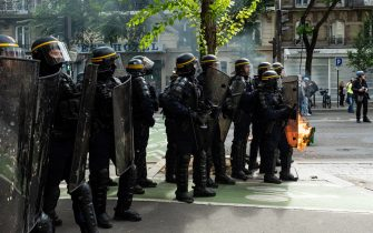 Anti-riot police officers standing near a burning trash can set on fire by demonstrators, while on July 14, 2021, 2 days after the last speech of the President of the French Republic Emmanuel Macron to introduce mandatory vaccination of caregivers and the generalization of the Sanitary Pass in public places of more than 50 people to cope with a resurgence of Covid in France following the emergence of the Delta variant, several hundred people gathered in the streets of Paris to demonstrate their opposition.  This demonstration was quickly repressed by the riot police creating clashes with the demonstrators, many of whom claimed to be Yellow Vests. (Photo by Samuel Boivin/NurPhoto)