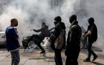 """TOPSHOT - A demonstrator kicks back a gas canister to Police on the sidelines of a protest in central Paris on July 14, 2021 against a governmental decision to impose Covid-19 tests for unvaccinated people who want to eat in restaurants or take long-distance trips, as the country looks to avoid a surge in more contagious Delta cases. - French President announced the tougher measures on July 12, including mandatory vaccinations for healthcare and retirement home workers, prompting a surge in bookings for the jab. But critics accused the president of discriminating against sceptics or those who will not be fully vaccinated before the """"health pass"""" rules come into effect. (Photo by GEOFFROY VAN DER HASSELT / AFP) (Photo by GEOFFROY VAN DER HASSELT/AFP via Getty Images)"""
