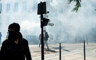 Demonstrators stand amidst a cloud of tear gas fired by the police, as on July 14, 2021, 2 days after the last speech of the President of the French Republic Emmanuel Macron to introduce mandatory vaccination of caregivers and the generalization of the Sanitary Pass in public places of more than 50 people to cope with a resurgence of Covid in France following the emergence of the Delta variant, several hundred people gathered in the streets of Paris to demonstrate their opposition.  This demonstration was quickly repressed by the riot police creating clashes with the demonstrators, many of whom claimed to be Yellow Vests. (Photo by Samuel Boivin/NurPhoto)