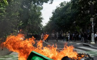 Demonstrators burned a trash can in a street in Paris, while on July 14, 2021, 2 days after the last speech of the President of the French Republic Emmanuel Macron to introduce mandatory vaccination of caregivers and the generalization of the Sanitary Pass in public places of more than 50 people to cope with a resurgence of Covid in France following the emergence of the Delta variant, several hundred people gathered in the streets of Paris to demonstrate their opposition.  This demonstration was quickly repressed by the riot police creating clashes with the demonstrators, many of whom claimed to be Yellow Vests. (Photo by Samuel Boivin/NurPhoto)
