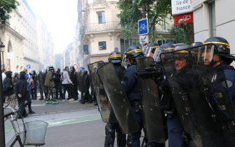 PARIS, FRANCE - JULY 14: Thousands of people, who opposed the mandatory new type of coronavirus (Covid-19) vaccine gather during a protest, on July 14, 2021 in Paris, France. Riot police intervened in protestors with tear gas, demonstrators clashed with the police, broke the windows of banks and shops, overturned trash cans and set up barricades on the roads. The demonstrators also set fire to garbage containers and construction equipment. (Photo by Alaattin Dogru/Anadolu Agency via Getty Images)