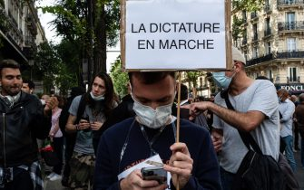 """A demonstrator holds up a sign against the government that reads """"La dictature En Marche"""", while on July 14, 2021, 2 days after the last speech of the President of the French Republic Emmanuel Macron to introduce mandatory vaccination of caregivers and the generalization of the Health Pass in public places of more than 50 people to cope with a resurgence of Covid in France following the emergence of the Delta variant, several hundred people gathered in the streets of Paris to demonstrate their opposition.  This demonstration was quickly repressed by the riot police creating clashes with the demonstrators, many of whom claimed to be Yellow Vests. (Photo by Samuel Boivin/NurPhoto)"""