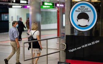 """VIENNA, AUSTRIA - SEPTEMBER 14: People wearing face masks pass by a sign reading """"Please cover your mouth and nose!"""" in the Karlsplatz underground station on September 14, 2020 in Vienna, Austria. Austrian Chancellor Sebastian Kurz announced yesterday that the country is seeing a second wave of coronavirus infections and he expects the number of daily newly reported cases to soon top 1,000. (Photo by Thomas Kronsteiner/Getty Images)"""