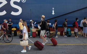 epa09323160 Travellers cary their luggage past a line of passengers queuing to board the Blue Star Delos passenger ferry, at the port of Piraeus near, Athens, Greece, 05 July 2021. Vaccinated passengers and the ones that hold a 72-hour negative covid-19 test are allowed to travel to the Greek islands, additionally all travelers must complete their health statement form before boarding their ship.  EPA/KOSTAS TSIRONIS