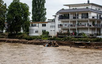 epa09349668 A digger is swept away in the flood water in Bad Neuenahr, Germany, 16 July 2021. Large parts of Western Germany were hit by heavy, continuous rain in the night to Wednesday, resulting in local flash floods that destroyed buildings and swept away cars.  EPA/CONSTANTIN ZINN