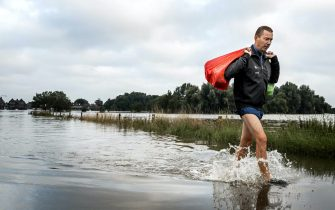 epa09349771 A man leaves a flooded house in evacuated Arcen, North Limburg, The Netherlands, 17 July 2021.  Heavy rainfall has led to floods and damages in various parts of the Netherlands and western Europe.  EPA/REMKO DE WAAL