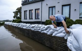 epa09349770 A resident of the evacuated Arcen looks at the rising water of the river Maas, in Arcen, North Limburg, The Netherlands, 17 July 2021.  Heavy rainfall has led to floods and damages in various parts of the Netherlands and western Europe.  EPA/REMKO DE WAAL