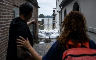 epa09349769 Two residents look at a flooded cafe in the evacuated Arcen, North Limburg, The Netherlands, 17 July 2021.  Heavy rainfall has led to floods and damages in various parts of the Netherlands and western Europe.  EPA/REMKO DE WAAL