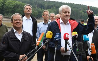 dpatop - 19 July 2021, North Rhine-Westphalia, Euskirchen: Federal Minister of the Interior Horst Seehofer (CSU, r) and the Minister President of North Rhine-Westphalia, Armin Laschet (CDU, l) speak to the media in front of the Steinbach Dam. The dam's dams were in danger of bursting for days due to the high water. Photo: Roberto Pfeil/dpa (Photo by Roberto Pfeil/picture alliance via Getty Images)