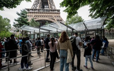 Visitors wait in line as they arrive to visit the Eiffel Tower in Paris, on July 16, 2021. - The Eiffel Tower reopened to visitors on July 16, 2021, after nine months of shutdown caused by the Covid pandemic. Up to 13,000 people per day will be allowed to take the elevators to the top and take in the views over the French capital, down from 25,000 in the pre-Covid era. (Photo by Bertrand GUAY / AFP) (Photo by BERTRAND GUAY/AFP via Getty Images)