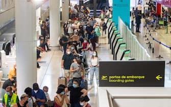Passeggeri in fila all'imbarco in un aeroporto portoghese