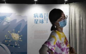 """WUHAN, CHINA - JULY 18: (CHINA OUT) A woman wears a mask while visiting the """"Enlightenment Of COVID-19"""" science exhibition on July 18, 2021 in Wuhan, Hubei Province, China.  The exhibition aims to explain the unique life form of the coronavirus and the thinking behind China's fight against the pandemic, as well as exploring ways to achieve a long-term coexistence with the virus. With no recorded cases of COVID-19 community transmissions since May 2020, life for residents in Wuhan is gradually returning to normal. (Photo by Getty Images)"""