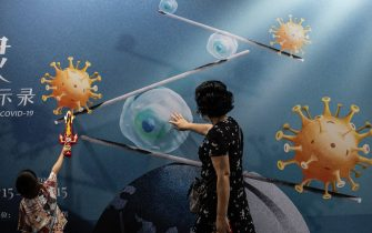 """WUHAN, CHINA - JULY 18: (CHINA OUT) A woman and child touch a display whilst visiting the """"Enlightenment Of COVID-19"""" science exhibition on July 18, 2021 in Wuhan, Hubei Province, China.  The exhibition aims to explain the unique life form of the coronavirus and the thinking behind China's fight against the epidemic, as well as exploring ways to achieve a long-term coexistence with virus. With no recorded cases of COVID-19 community transmissions since May 2020, life for residents in Wuhan is gradually returning to normal. (Photo by Getty Images)"""