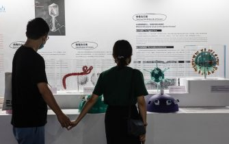 """WUHAN, CHINA - JULY 18: (CHINA OUT) A couple wears masks as they look at a display as they visit the """"Enlightenment Of COVID-19"""" science exhibition on July 18, 2021 in Wuhan, Hubei Province, China.  The exhibition aims to explain the unique life form of the coronavirus and the thinking behind China's fight against the epidemic, as well as exploring ways to achieve a long-term coexistence with virus. With no recorded cases of COVID-19 community transmissions since May 2020, life for residents in Wuhan is gradually returning to normal. (Photo by Getty Images)"""