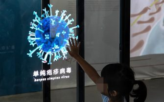"""WUHAN, CHINA - JULY 18: (CHINA OUT) A child touches a light show of Herpes simplex virus display whilst visiting the """"Enlightenment Of COVID-19"""" science exhibition on July 18, 2021 in Wuhan, Hubei Province, China.  The exhibition aims to explain the unique life form of the coronavirus and the thinking behind China's fight against the pandemic, as well as exploring ways to achieve a long-term coexistence with the virus. With no recorded cases of COVID-19 community transmissions since May 2020, life for residents in Wuhan is gradually returning to normal. (Photo by Getty Images)"""