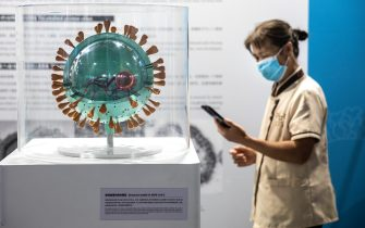 """WUHAN, CHINA - JULY 18: (CHINA OUT) A cleaner wears a mask while clean the kinds of virus model at the """"Enlightenment Of COVID-19"""" science exhibition in Wuhan Natural History Museum on July 18, 2021 in Wuhan, Hubei Province, China.  The exhibition aims to explain the unique life form of the coronavirus and the thinking behind China's fight against the pandemic, as well as exploring ways to achieve a long-term coexistence with the virus. With no recorded cases of COVID-19 community transmissions since May 2020, life for residents in Wuhan is gradually returning to normal. (Photo by Getty Images)"""