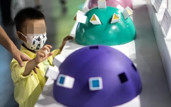 """WUHAN, CHINA - JULY 18: (CHINA OUT)A child will touch a display whilst visiting the """"Enlightenment Of COVID-19"""" science exhibition on July 18, 2021 in Wuhan, Hubei Province, China.  The exhibition aims to explain the unique life form of the coronavirus and the thinking behind China's fight against the pandemic, as well as exploring ways to achieve a long-term coexistence with the virus. With no recorded cases of COVID-19 community transmissions since May 2020, life for residents in Wuhan is gradually returning to normal. (Photo by Getty Images)"""