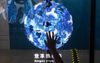 """WUHAN, CHINA - JULY 18: (CHINA OUT) A child touches a light show of the Dengue virus display whilst visiting the """"Enlightenment Of COVID-19"""" science exhibition on July 18, 2021 in Wuhan, Hubei Province, China.  The exhibition aims to explain the unique life form of the coronavirus and the thinking behind China's fight against the pandemic, as well as exploring ways to achieve a long-term coexistence with the virus. With no recorded cases of COVID-19 community transmissions since May 2020, life for residents in Wuhan is gradually returning to normal. (Photo by Getty Images)"""