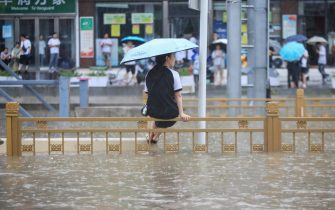 This photo taken on July 20, 2021 shows a woman sitting on a fence on a flooded street following heavy rains in Zhengzhou in China's central Henan province. - - China OUT (Photo by STR / AFP) / China OUT (Photo by STR/AFP via Getty Images)