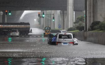 TOPSHOT - This photo taken on July 20, 2021 shows people pushing a van through flood waters along a street following heavy rains in Zhengzhou in China's central Henan province. - - China OUT (Photo by STR / AFP) / China OUT (Photo by STR/AFP via Getty Images)