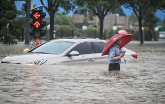 This photo taken on July 20, 2021 shows a man wading past a submerged car along a flooded street following heavy rains in Zhengzhou in China's central Henan province. - - China OUT (Photo by STR / AFP) / China OUT (Photo by STR/AFP via Getty Images)